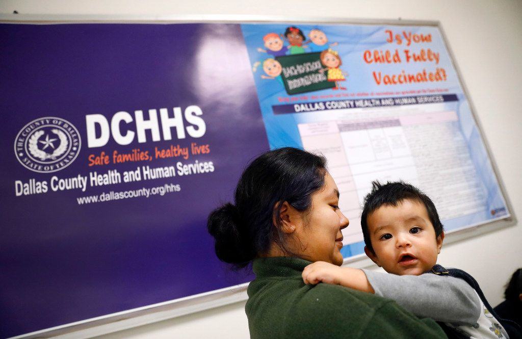 Vanessa Esquivel of Mesquite waits for an influenza shot for her 8-month-old son, Juan, at the Dallas County Health and Human Services Immunization Clinic in Dallas in December.