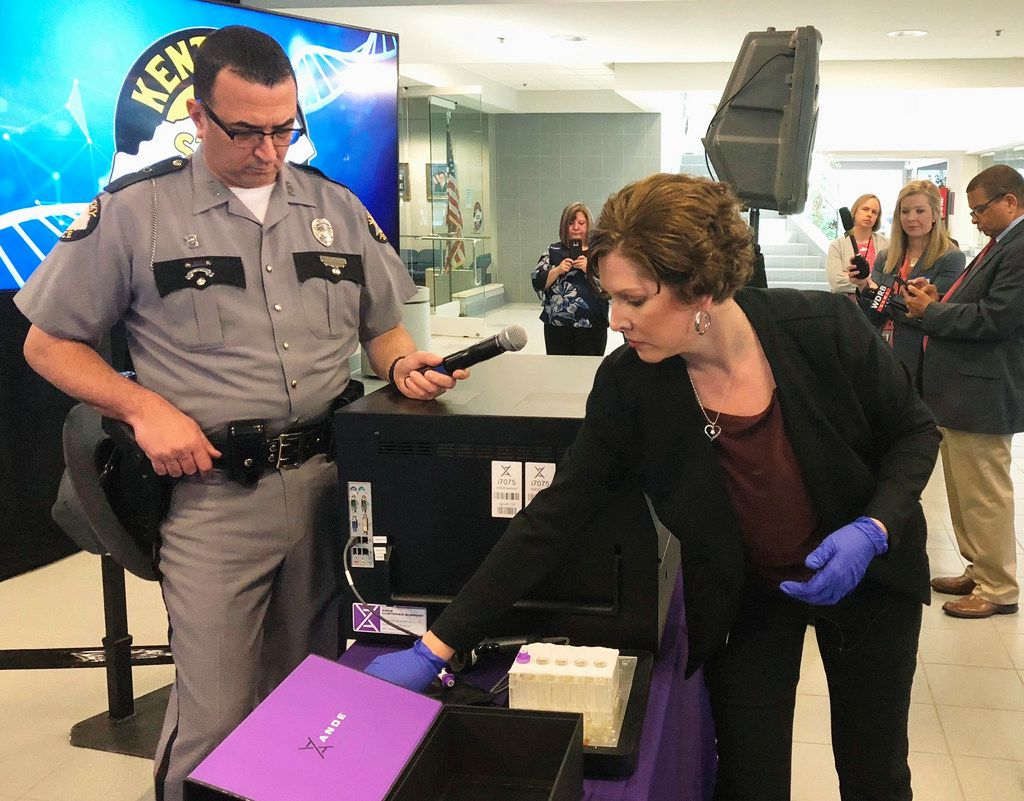 In this April 10, 2019, file photo, Regina Wells, foreground right, a forensic laboratories supervisor with the Kentucky State Police, demonstrates new crime-fighting technology in Frankfort, Ky. Rapid DNA machines roughly the size of an office printer have helped solve rape cases in Kentucky. Now a state board in Texas has asked a growing government provider of the DNA equipment used in those high-profile projects to halt work amid concerns of potentially jeopardized criminal cases, according to a letter obtained by The Associated Press. (AP Photo/Bruce Schreiner, File)