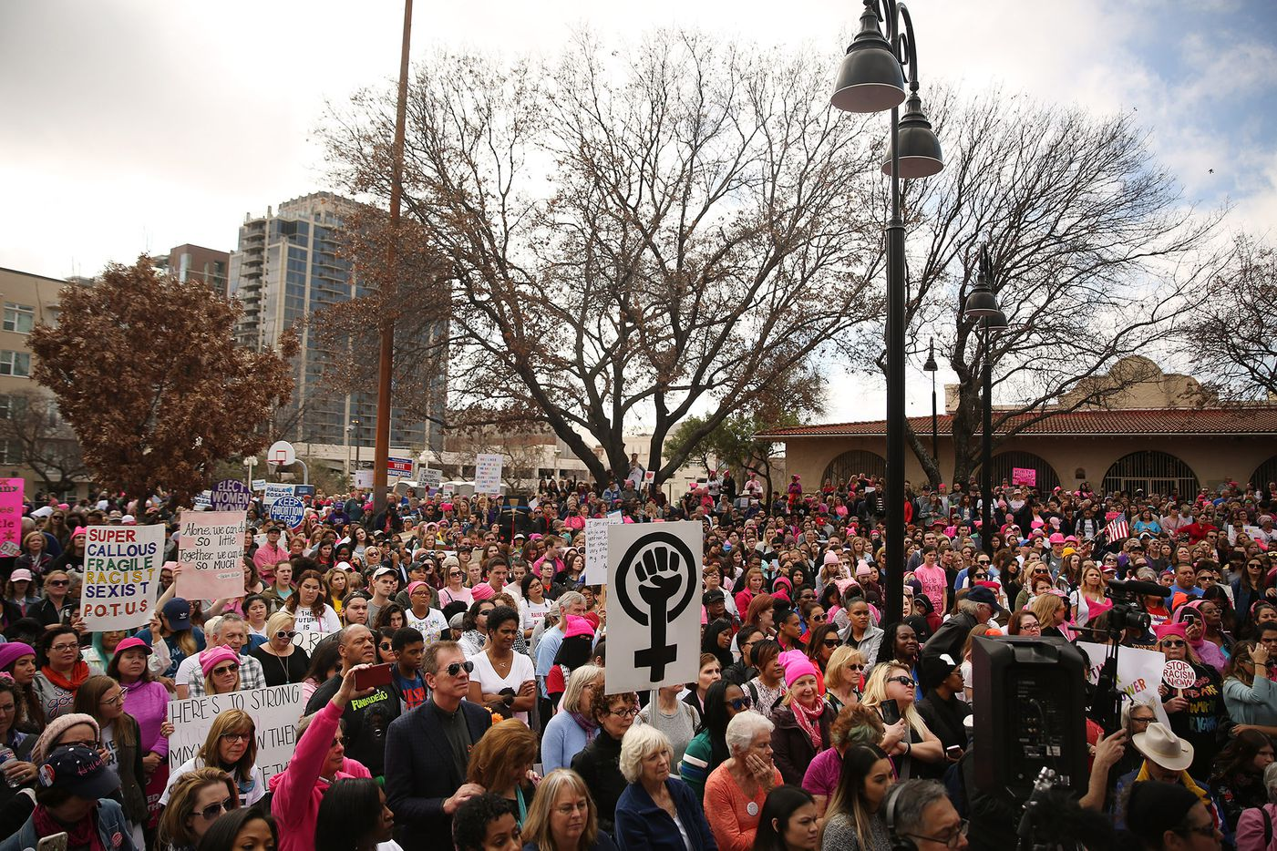 Marchers listens as speakers make comments at Pike Park during the rally portion of the Dallas Women's March in Dallas Saturday.