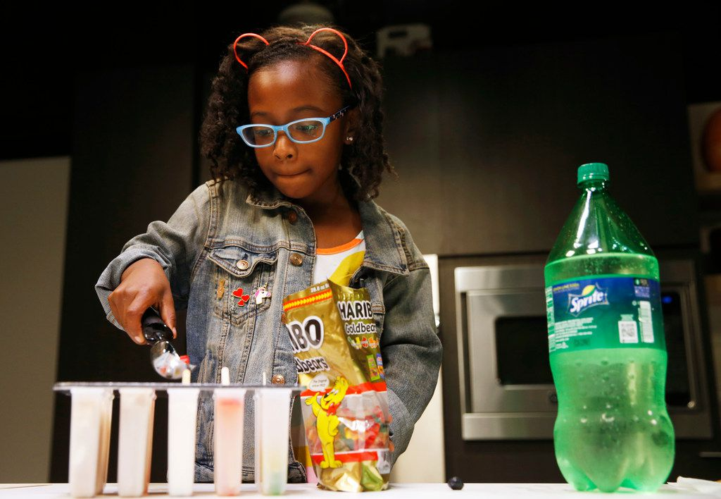 Ellington Young, 7, makes a gummy bear and lemon lime soda ice pop in Dallas.