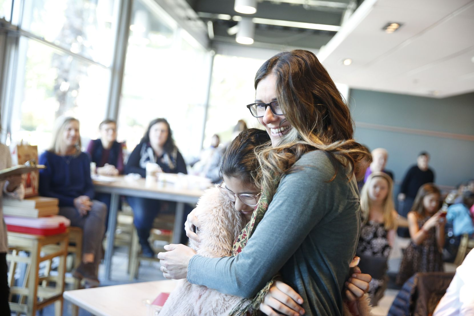 Sheila Bustillos hugs her daughter after winning in The Dallas Morning News cookie contest at Central Market in Dallas on Nov. 14, 2018.