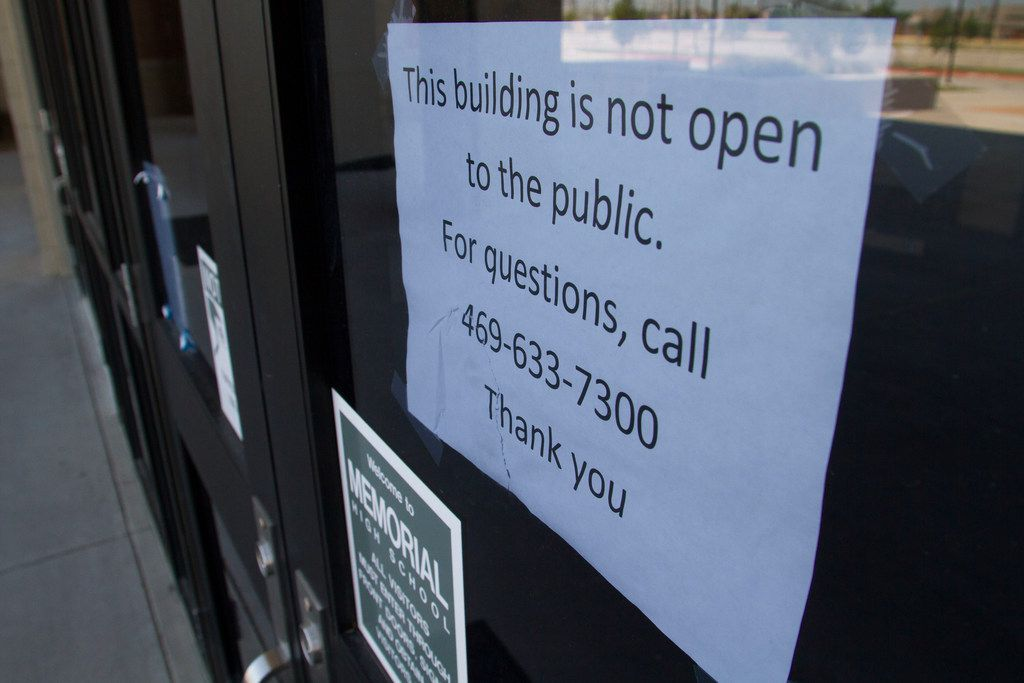 A sign is posted on the front door of Memorial High School, which is set to open in August 2018 after sitting empty for a year because of budget issues in Frisco ISD.