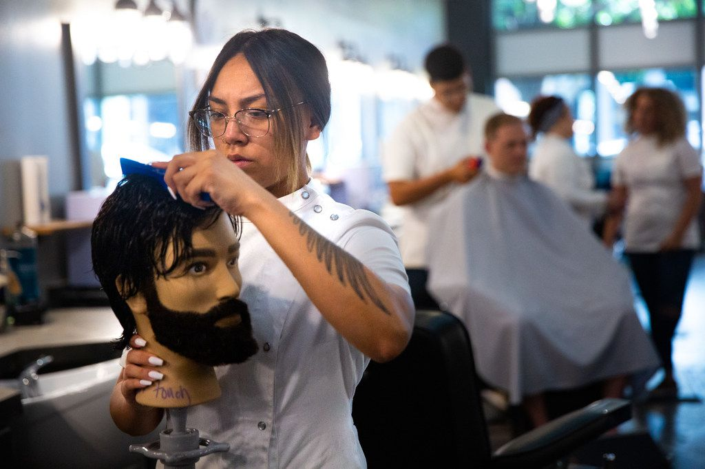 Student Megan Yruegas practices sectioning hair on a mannequin at the Blade Craft Barber Academy in the Deep Ellum neighborhood of Dallas on Thursday, Aug. 1, 2019.