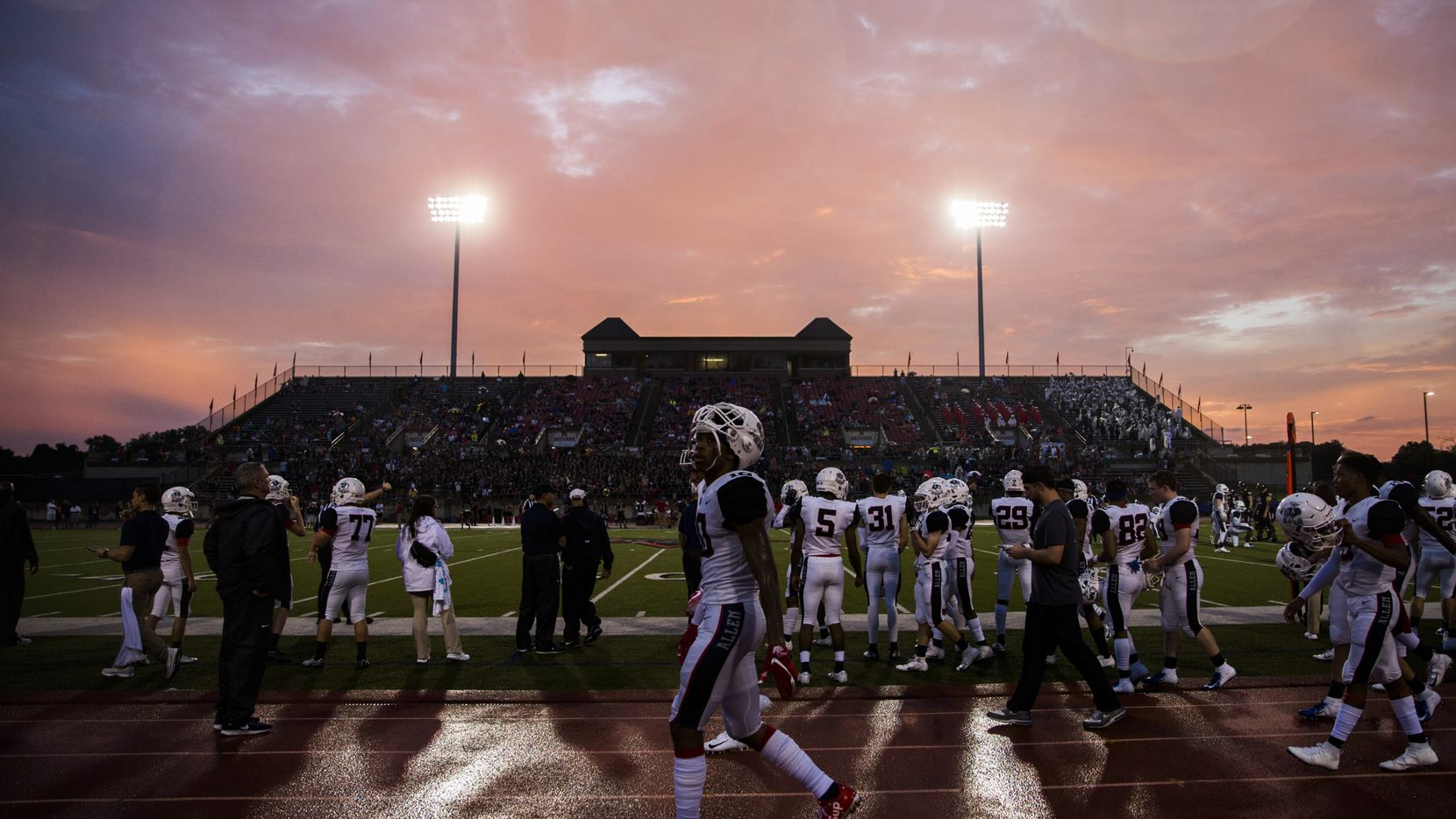 Allen football players walk along the sideline as rain falls and the sun sets during the third quarter of a high school football game between Allen and Coppell on Sept. 14.