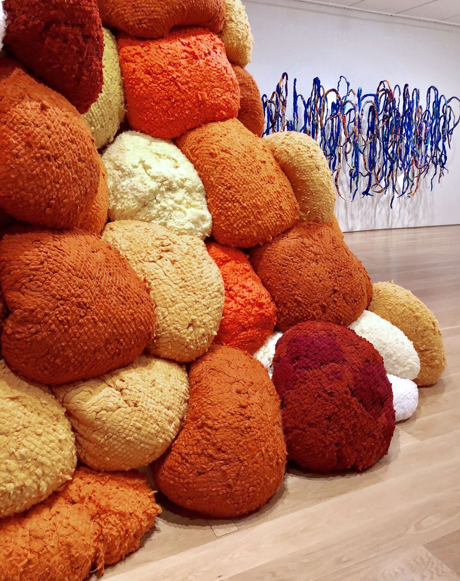 """""""Sentinel of Saffron,"""" 2018, and """"Ba li Chords,"""" 2014-15, part of the """"Sheila Hicks: Seize, Weave Space"""" 2019 installation, on view through Aug. 18 at the Nasher Sculpture Center in Dallas."""