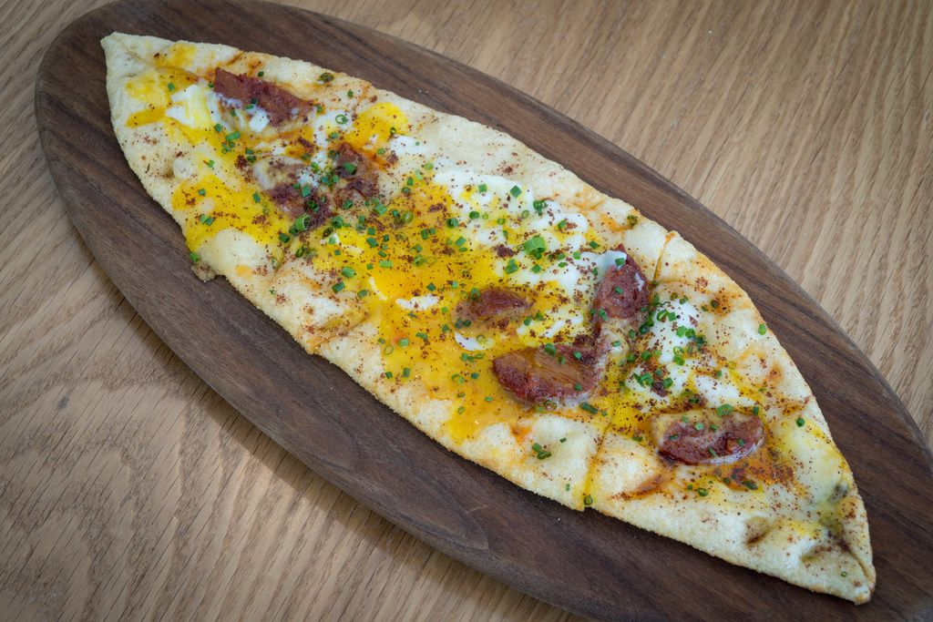 Soujouk pide is a boat-shaped flatbread from the wood-burning oven, topped with spicy sausage, kasar cheese and a slightly runny egg.