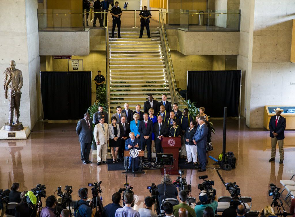 Texas Governor Greg Abbott and Dallas Mayor Mike Rawlings speak during a press conference on Friday, July 8, 2017 at Dallas City Hall in downtown Dallas, Texas. They stood in front of a group of Dallas city councilmen, state representatives, state senators and Texas Attorney General Ken Paxton (center). They made comments about a shooting on Thursday, July 7, 2016 in downtown Dallas that targeted police officers and left five people dead and seven more injured. (Ashley Landis/The Dallas Morning News)