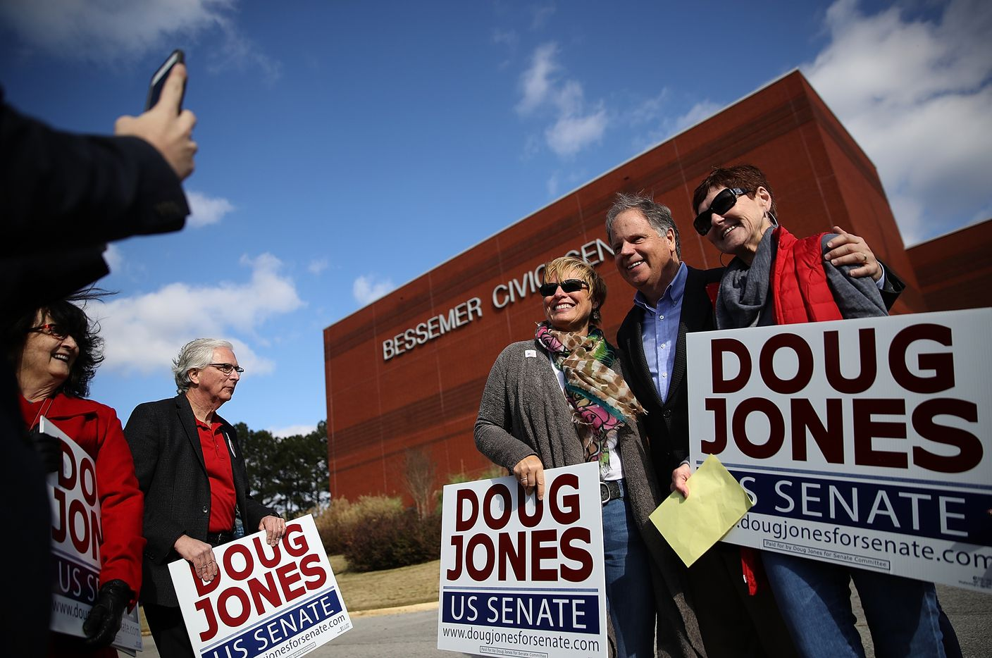 Doug Jones mingled with voters outside a polling station in Bessemer, Ala., on Tuesday.