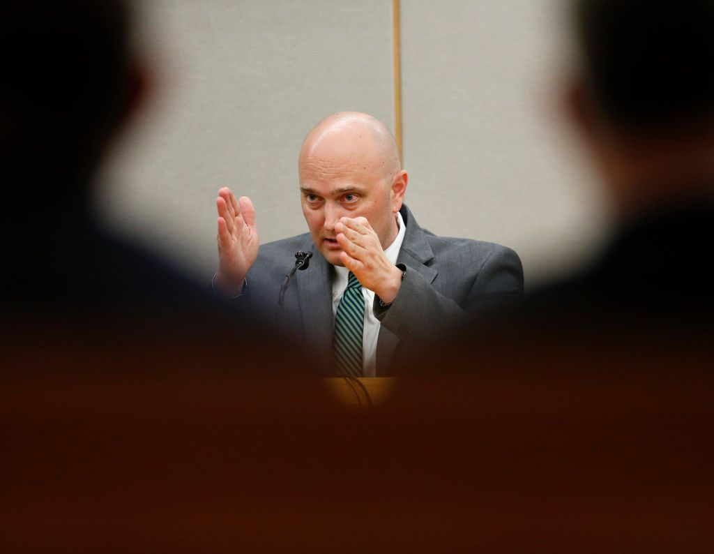 Fired Balch Springs police officer Roy Oliver, who is charged with the murder of 15-year-old Jordan Edwards, motions with his hands when describing his field of vision on the car that Jordan Edwards was in while testifying with defense attorney Jim Lane during the sixth day of his trial at the Frank Crowley Courts Building in Dallas on Aug. 23, 2018.
