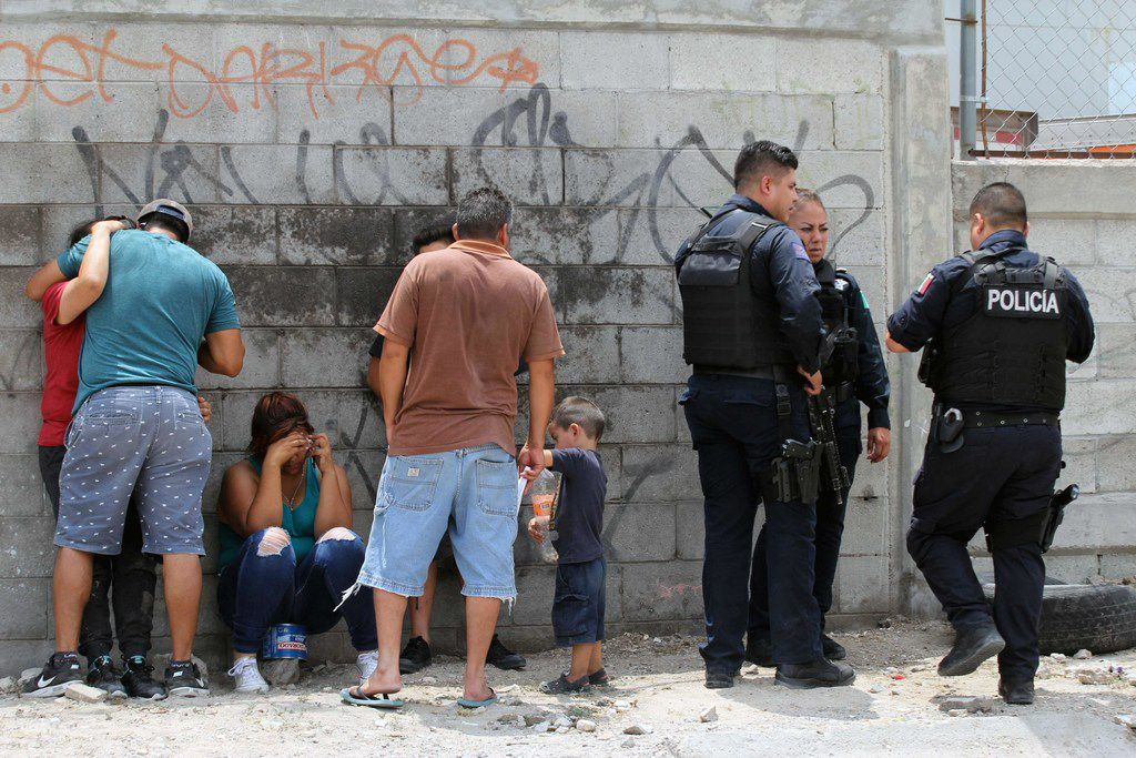Policemen stood next to relatives waiting for the bodies of their beloved ones following the killing of 11 people inside a house in Ciudad Juarez, Mexico, on Friday.