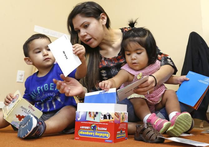 Elizabeth Mancilla, a teacher at ChildCareGroup in Oak Cliff, helps Martin Correa, 2 1/2 and Andrea Ramirez, 19 months, get their hands on as many learning exercises as possible.
