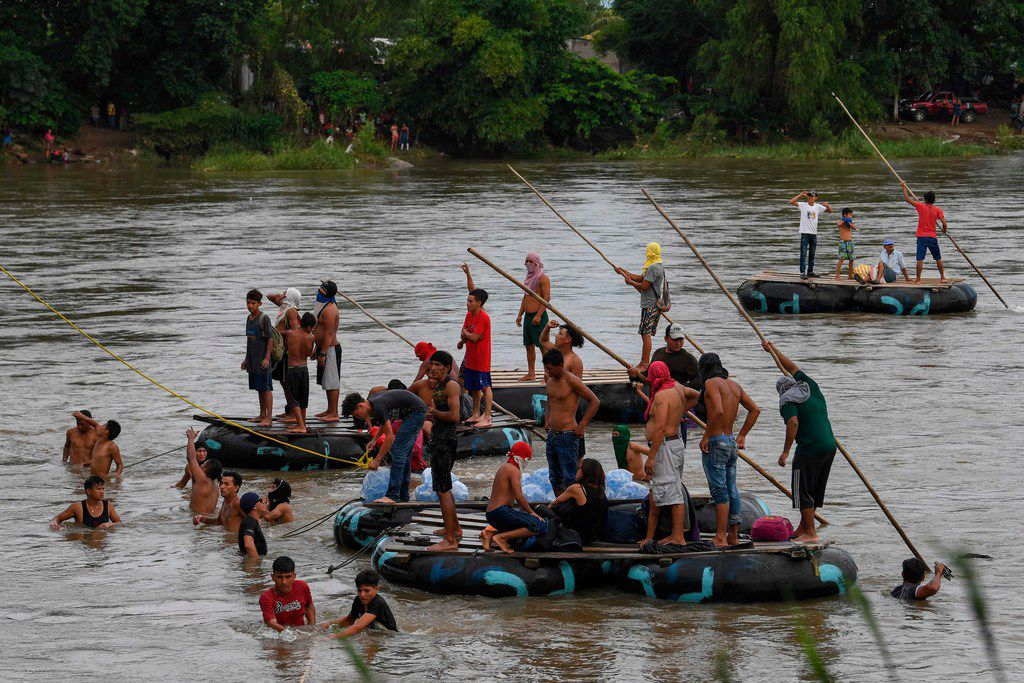 The migrants await for fellow migrants to jump from the bridge to swim or board a raft to reach Mexico in Ciudad Hidalgo, Chiapas state, Mexico, on October 19, 2018.