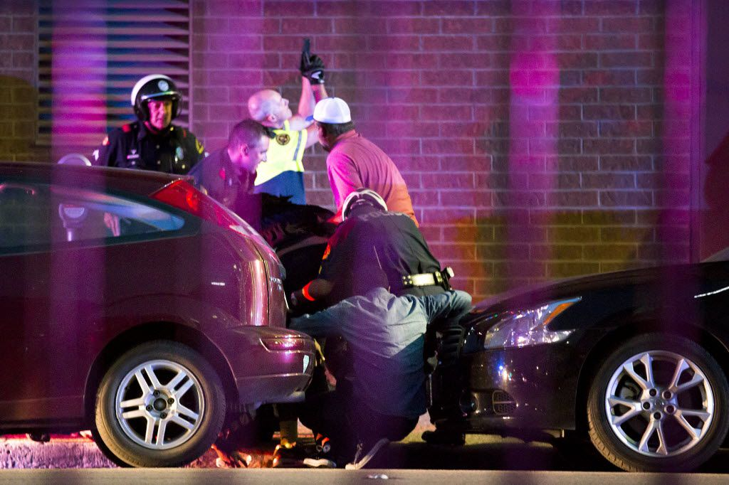 Shetamia Taylor (hunched over, in dark shirt, center) who was shot in the leg, is helped by Dallas police officers as they shield civilians and evacuate them from a position between two parked cars on Lamar Street between Main and Commerce after shots were fired during a Black Lives Matter rally in downtown Dallas on Thursday, July 7, 2016. As the rally and march were winding down, Micah Xavier Johnson, 25, opened fire in an attack that killed five police officers.