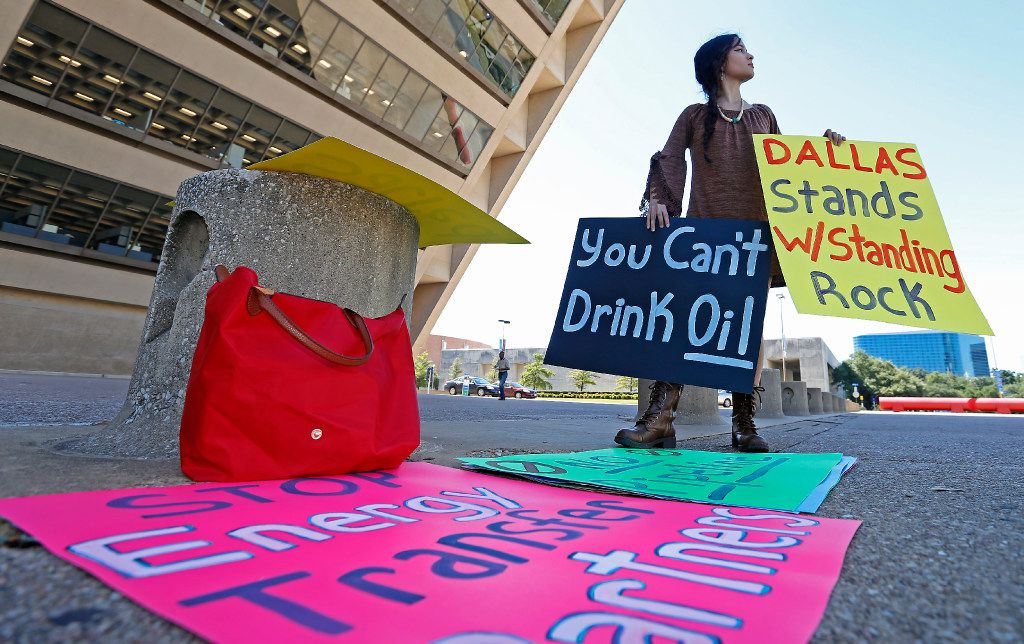 Environmental activist Victoria Guevara holds signs to protest against construction of the Dakota Access Pipeline at Dallas City Hall in Dallas, Tuesday, Oct. 11, 2016.
