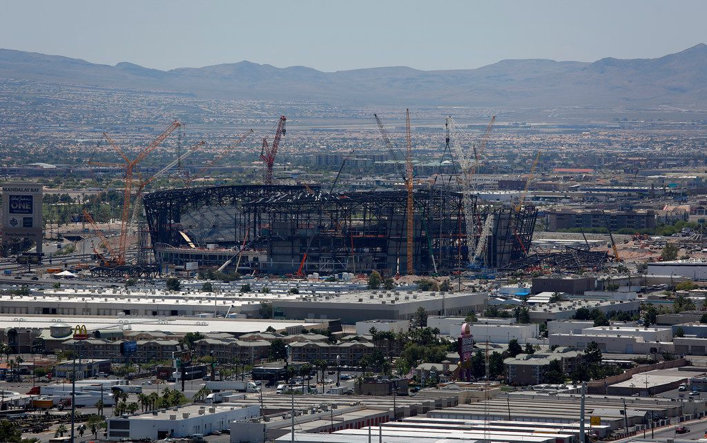 Construction cranes surround the future NFL Raiders football stadium Tuesday, June 4, 2019, in Las Vegas. The Las Vegas Bowl is moving to the new stadium next year, and will feature teams from the SEC or Big Ten conferences against a Pac-12 contender. (AP Photo/John Locher)
