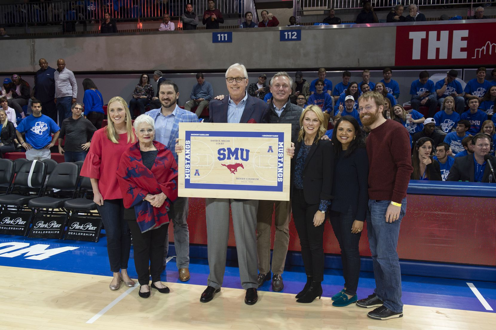 David Miller (center) held a piece of flooring as he stood with his family on Dec. 5, 2018, when the university announced that it was naming the basketball court in his honor.