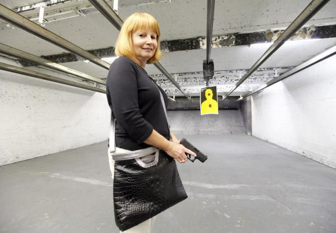 Jean Rosandich holds a Glock at the Shooter Shop in West Allis, Wis., as she models a handbag by Been & Badge that's equipped to safely carry handguns. Holsters can be inserted and adjusted for comfort and efficiency, in case a woman needs to get to her handgun in a hurry.