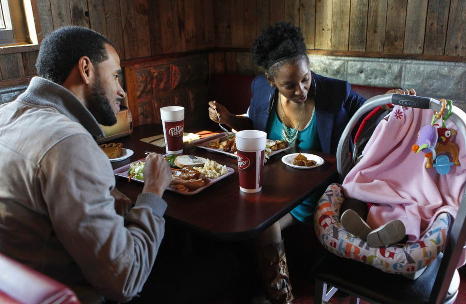 Anthony and Autumn Balfour sit with their baby, Fallon, 5-month old, while enjoying a free Thanksgiving Day meals at The Slow Bone in 2014.