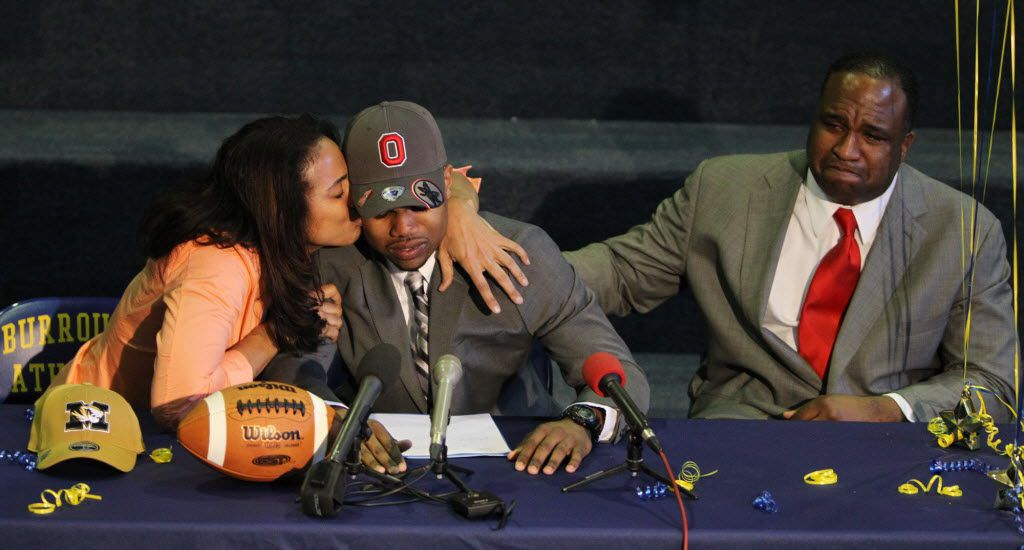 John Burroughs running back Ezekiel Elliott receives a kiss from his mother, Dawn Elliott, after announcing his committment to Ohio State University on Wednesday, Feb. 6, 2013, at John Burroughs School in St. Louis.  At right is Ezekiel's father, Elliott.  Both of his parents attended the University of Missouri. (Chris Lee/St. Louis Post-Dispatch)