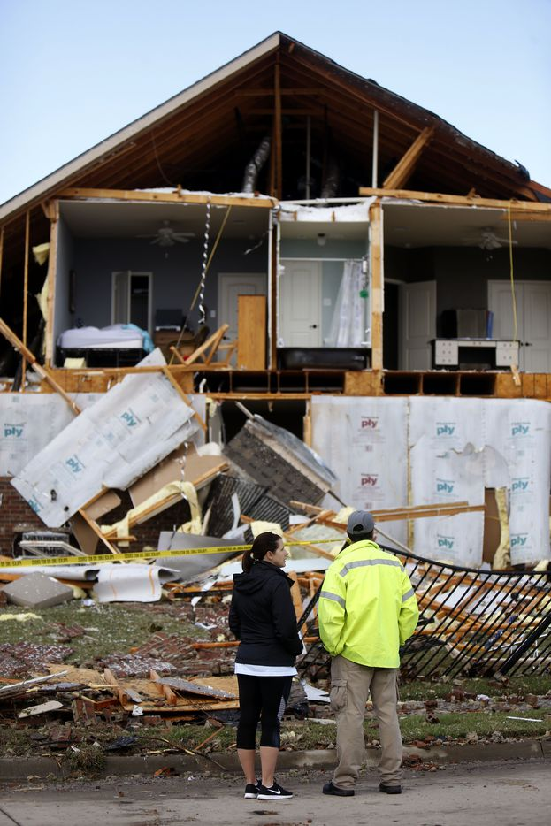 Dennis Dayman, an operations officer with the Rockwall Fire Department, stands with his wife Jennifer Dayman outside a damaged home along Tumbleweed Circle following a storm in the early hours of the morning in Rockwall, Texas on Wednesday, March 29, 2017. (Rose Baca/The Dallas Morning News)