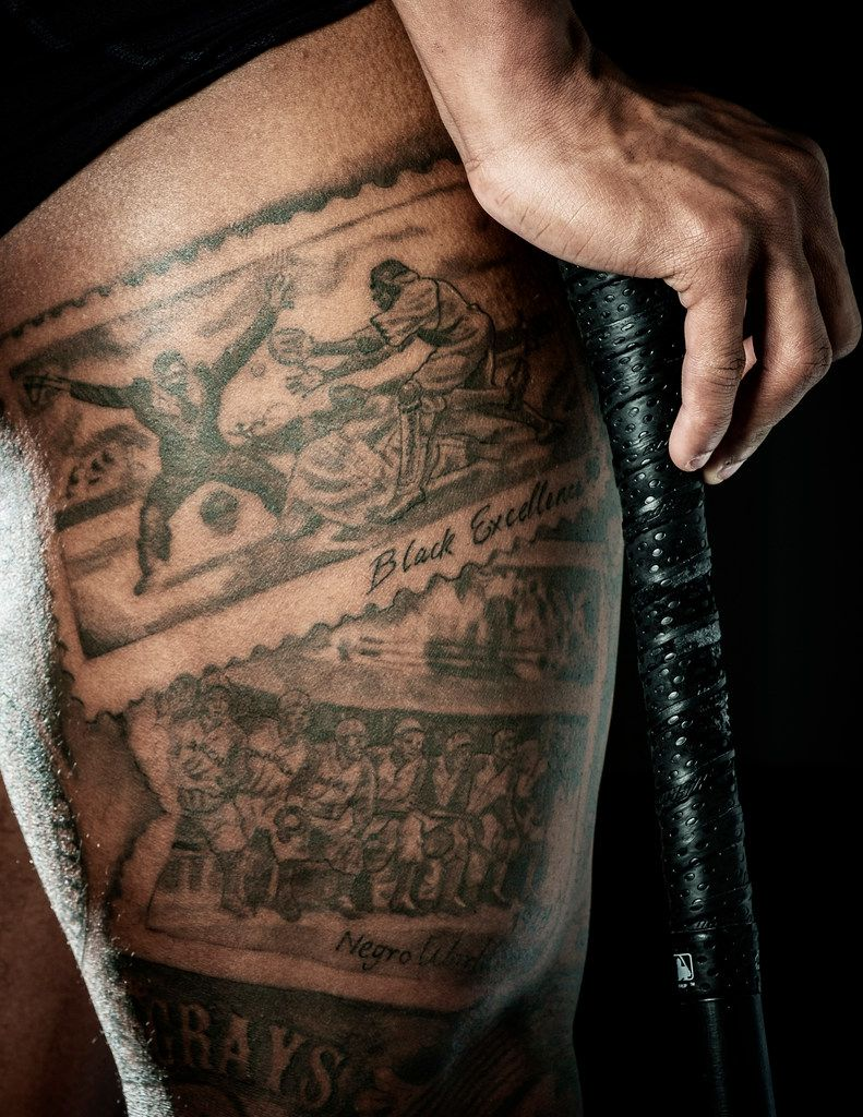 The scene of a player sliding into home from a USPS stamp honoring the Negro Leauges is featured in new tattoos on the thigh of Texas Rangers outfielder Delino DeShields after a workout at the team's spring training facility at on Monday, Feb. 25, 2019, in Surprise, Ariz.. During the offseason DeShields added tattoos to his right leg that are all dedicated to the Negro Leagues. (Smiley N. Pool/The Dallas Morning News)