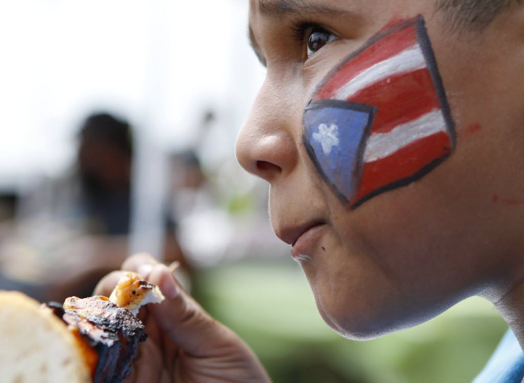 Tomas Garcia, 10, with a Puerto Rican flag painted on his face, eats during a cookout at a Chinchorro party, hosted by the Puerto Rican Association of Dallas, on May 21, 2016 in Fort Worth.