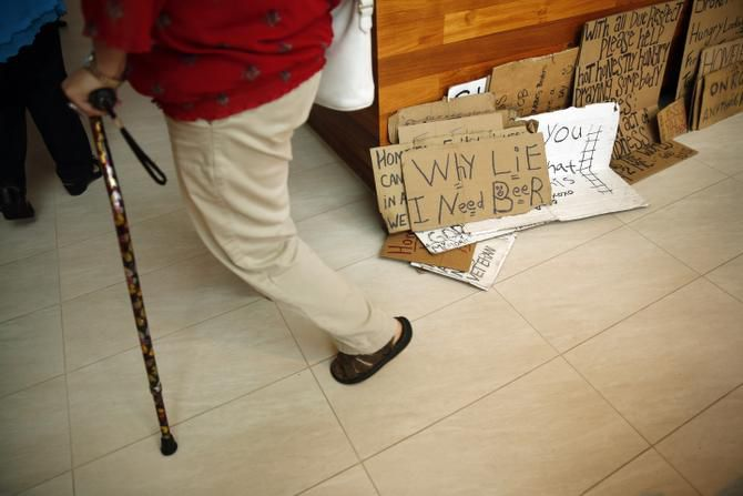 Signs near the front door at a party welcoming Baronet back from his 31-day cross-country trip showed the variety of messages on panhandlers' minds.