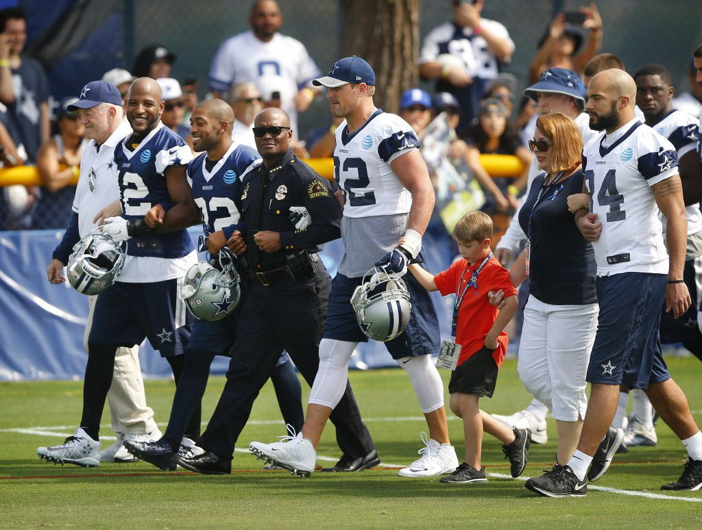 Dallas police Chief David Brown (center) walked arm-in-arm with (from left) Dallas Cowboys owner Jerry Jones, strong safety Barry Church (42), cornerback Orlando Scandrick (32), tight end Jason Witten (82) Magnus Ahrens, 8, (son of slain Dallas officer Lorne Ahrens), his aunt Erika Swyryn, and tight end James Hanna (84) before opening day of training camp in Oxnard, California, Saturday, July 30, 2016. (Tom Fox/The Dallas Morning News)  -- MANDATORY CREDIT, NO SALES, MAGS OUT, TV OUT, INTERNET USE BY AP MEMBERS ONLY