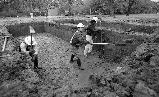 11-17-94..Francisco  Navarrette, (L), Crescencio Cortez, (M), and Modesto Arana, (R),  of Rosiek construction company, work on one of the graves thats  being dug at Freedman's Cemetery located at Central and Lemmon  avenue in Dallas. 1,513 people will be re- buried at this site by  12-2-94.
