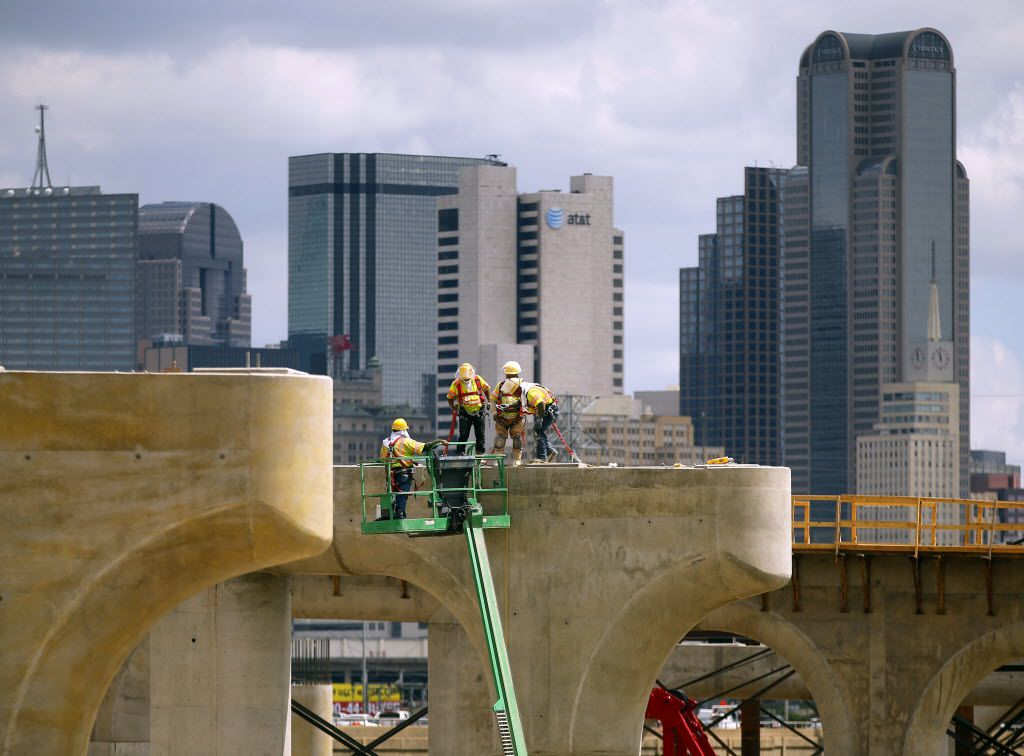 Construction crews worked in 2014 atop the bridge support columns and tops of the new northbound Interstate 35E bridge leading to downtown Dallas, a part of the massive Dallas Horseshoe Project, The project was done by Pegasus Link Contractors, the joint venture between Fluor Enterprises and Balfour Beatty Infrastructure.