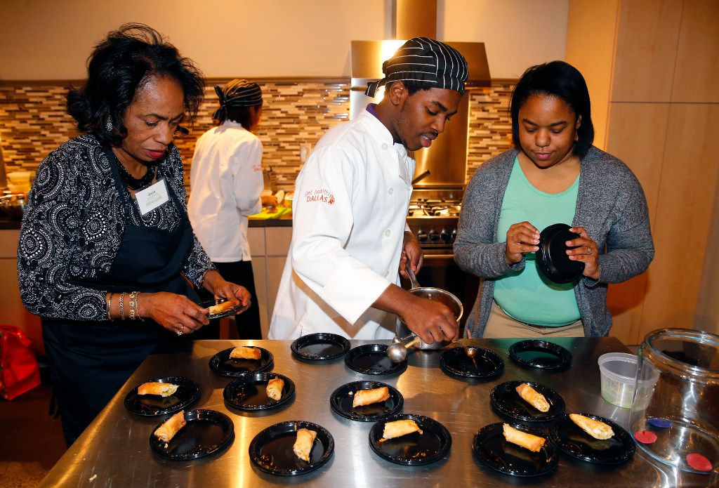 Lincoln High School culinary chef Paula Lewis (right) helps Juwan Grant  prepare a plate of Chinese spring rolls with shrimp and chili sauce at the Food in Fashion event at 3015 in the Trinity Groves.