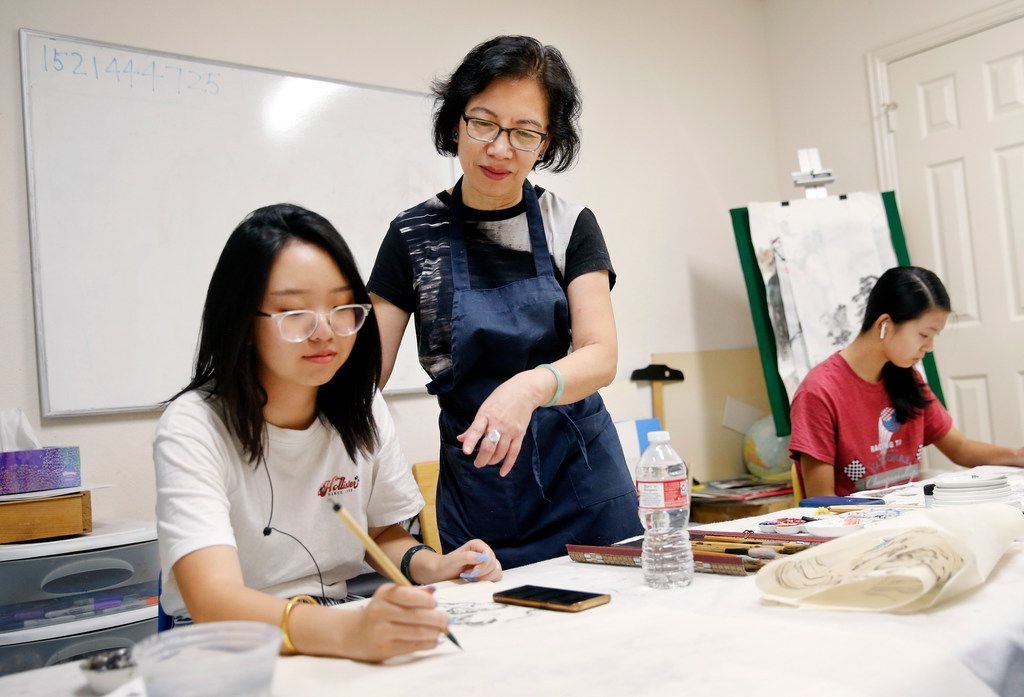 Local artist Jenney Chang (center) works with Katherine Wang, 19, of Plano, on Wang's Gong Bi style Chinese painting at Chang's Plano home studio on Aug. 11, 2019. Wang has been taking lessons from Chang since she was 6 years old.