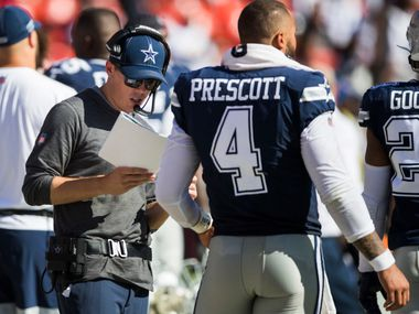 Cowboys offensive coordinator Kellen Moore (left) talks with quarterback Dak Prescott (4) on the sideline during the fourth quarter of a game against the Washington Redskins on Sunday, Sept. 15, 2019, at FedExField in Landover, Md.
