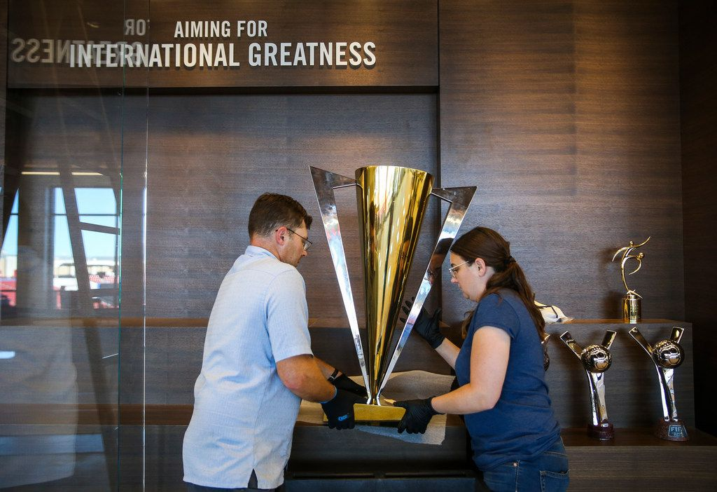 Art handler Bob Treece, left, and mount maker Deanna Hovey move a CONCACAF trophy into a display case at the National Soccer Hall of Fame on Wednesday, Oct. 10, 2018 in Frisco, Texas.