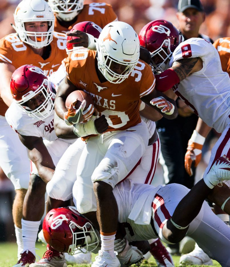 Texas Longhorns running back Toneil Carter (30) is tackled by Oklahoma Sooners defenders during the second quarter of the AT&T Red River Showdown college football game between the University of Texas and Oklahoma University on Saturday, October 14, 2017 at the Cotton Bowl in Fair Park in Dallas. (Ashley Landis/The Dallas Morning News)
