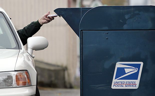 A U.S. Postal Service customer drops mail into a curbside mailbox on Dec. 5, 2011 in Seattle. The Postal Service is planning to close as many as 252 processing centers next spring in order to cut costs, a move that would eliminate the possibility of next-day delivery of mail sent first class.