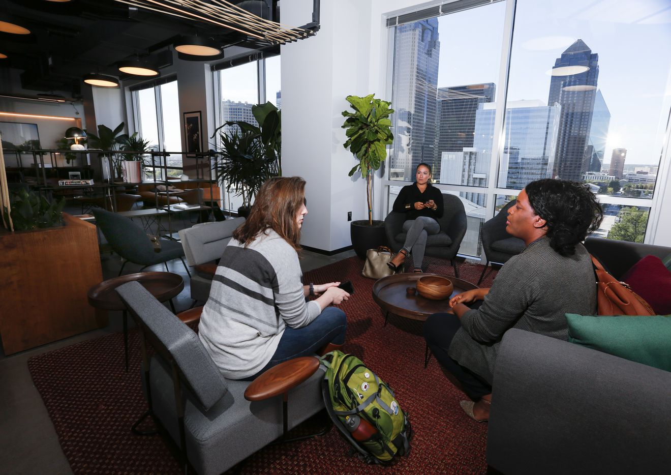 From left: Caitlin Studley, Clarisa Lindenmeyer and Jasmin Brand, all with Launch DFW, gather in one of the common areas at Industrious,  a co-working office on the ninth floor of One Arts Plaza in downtown Dallas.