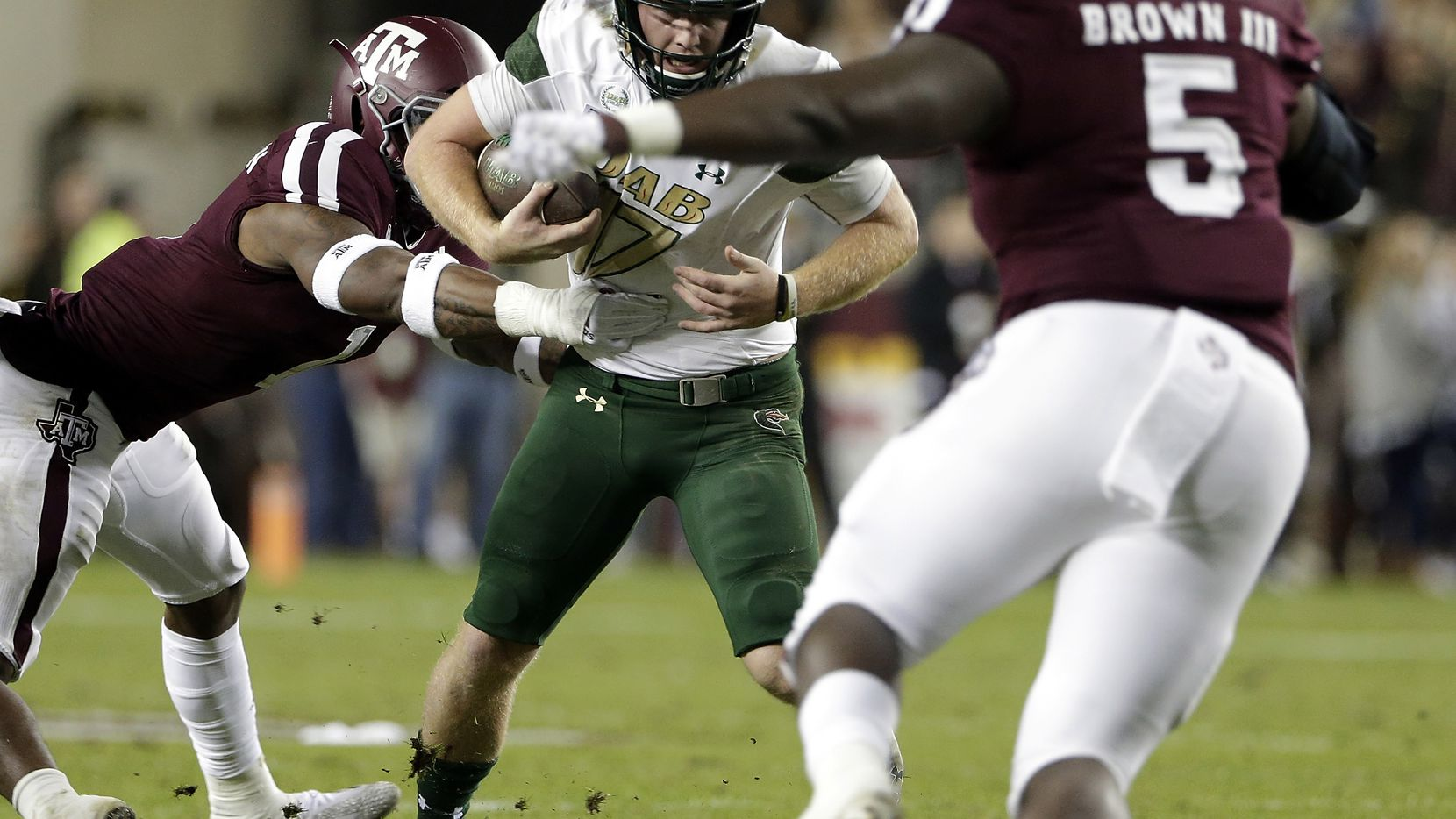 FILE - UAB quarterback Tyler Johnston III (17) is caught on a keeper play between Texas A&M linebacker Buddy Johnson, left, and defensive lineman Bobby Brown III, right, during the first half of a game Saturday, Nov. 17, 2018, in College Station. (AP Photo/Michael Wyke)