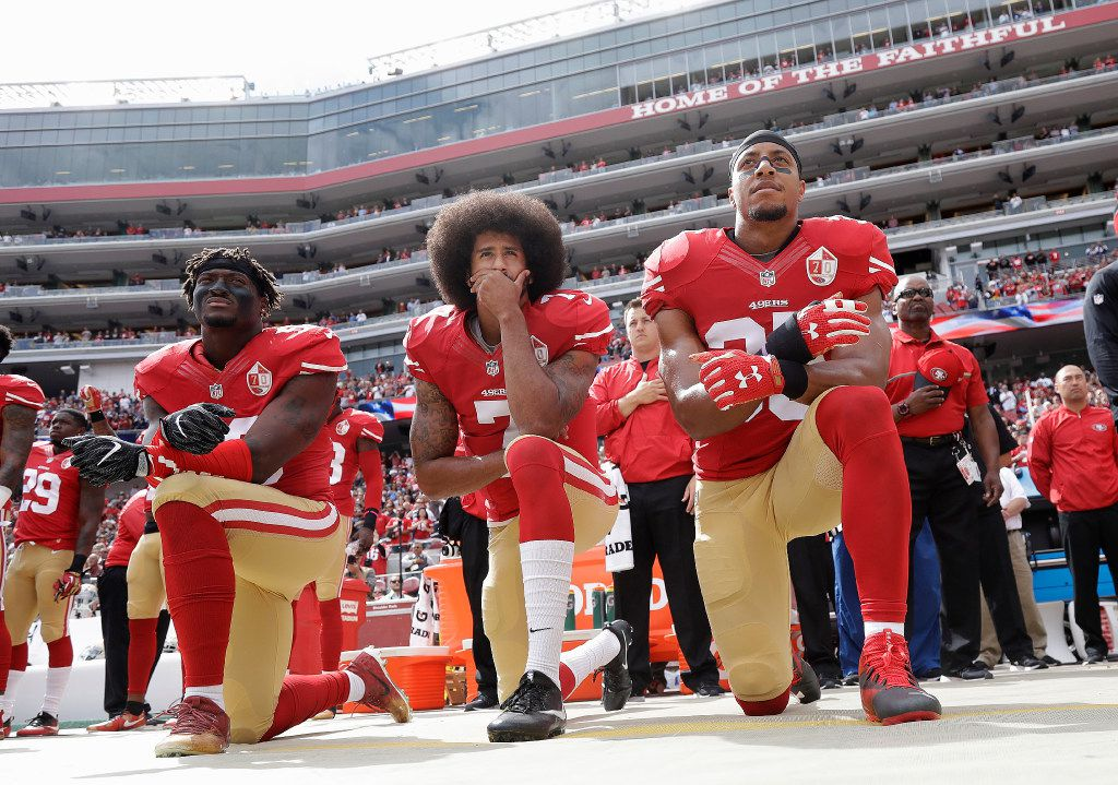 San Francisco 49ers outside linebacker Eli Harold, left, quarterback Colin Kaepernick, center, and safety Eric Reid kneel during the national anthem before an NFL football game against the Dallas Cowboys in Santa Clara, Calif., Sunday, Oct. 2, 2016. (AP Photo/Marcio Jose Sanchez)