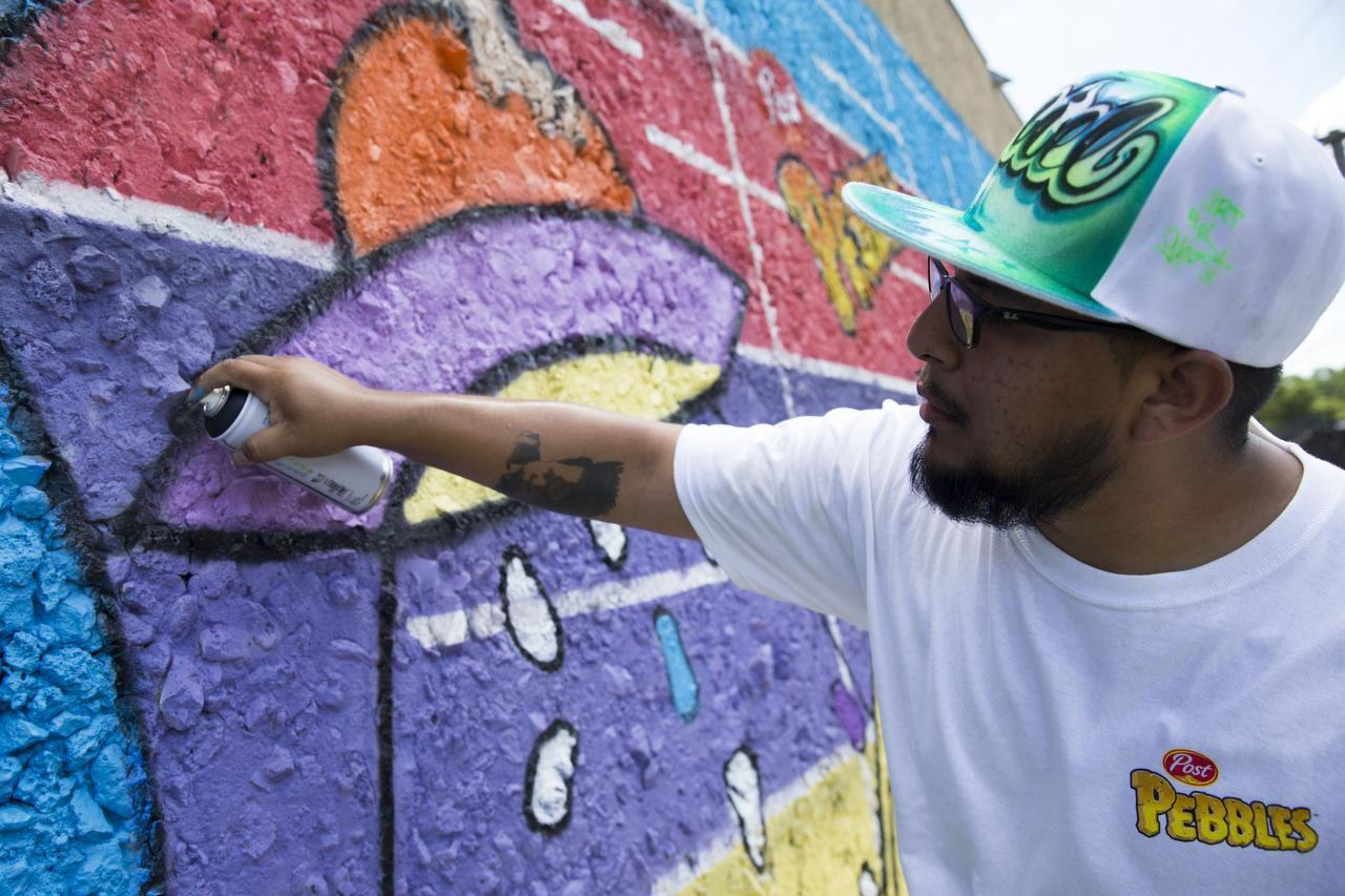 Daniel Yanez le da los toques finales a un mural que él diseñó y que pintó con la ayuda de 200 niños. TING SHEN/DMN