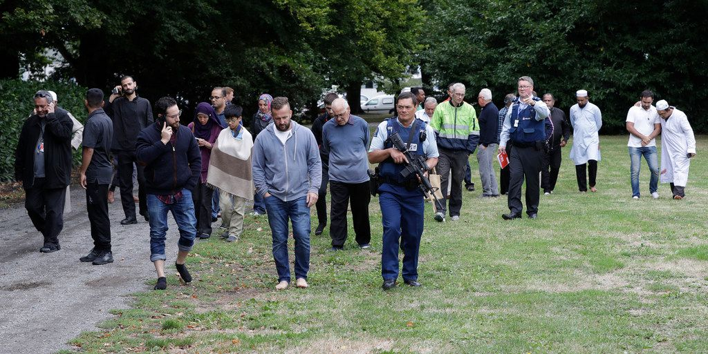 Police escort witnesses away from a mosque in central Christchurch, New Zealand, Friday.