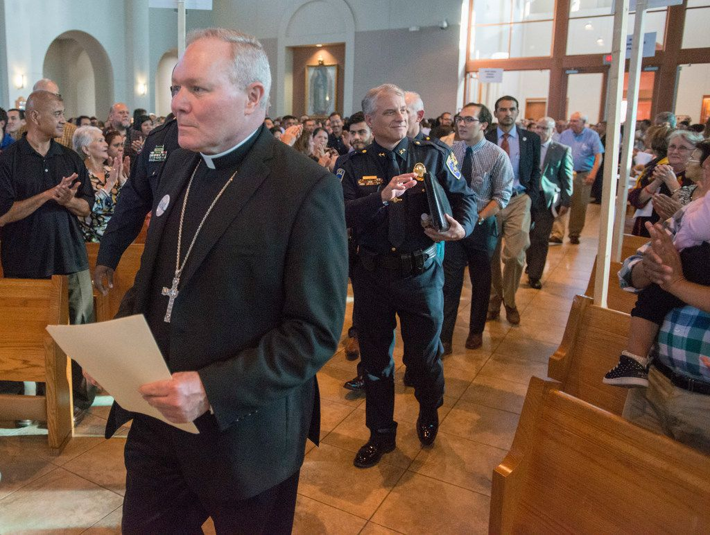 Rev. Edward J. Burns, left, bishop of the Roman Catholic Diocese of Dallas is followed a procession of clergy, law enforcement officials and Dallas-area city officials to the dais at Mary Immaculate Catholic Church in Farmers Branch for a Dallas Area Interfaith meeting on immigration, policing and city infrastructure Sunday November 5, 2017 in Farmers Branch, Texas.