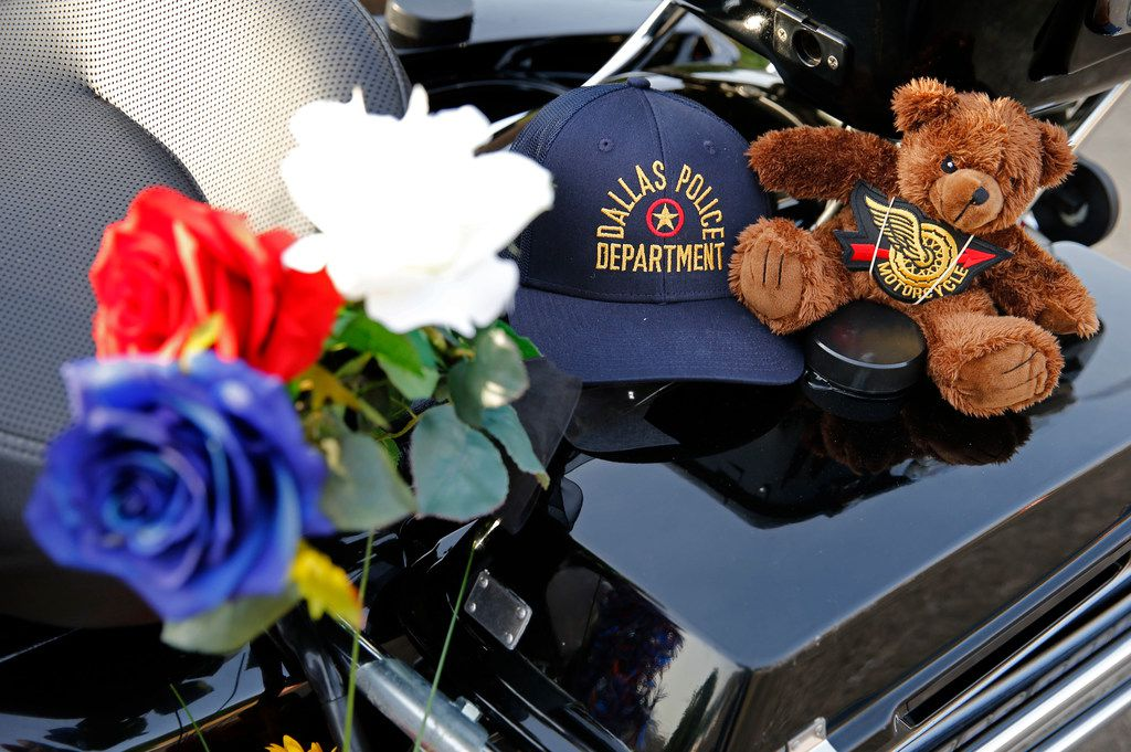"""Flowers and notes are left at a memorial for Dallas police Senior Cpl. Earl """"Jamie"""" Givens at the Dallas Police Department's Central Patrol substation in Dallas."""