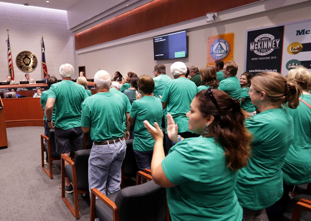 Mckinney residents show their opposition regarding a plan to expand U.S. Highway 380 during a city council meeting at McKinney City Hall on July 17.
