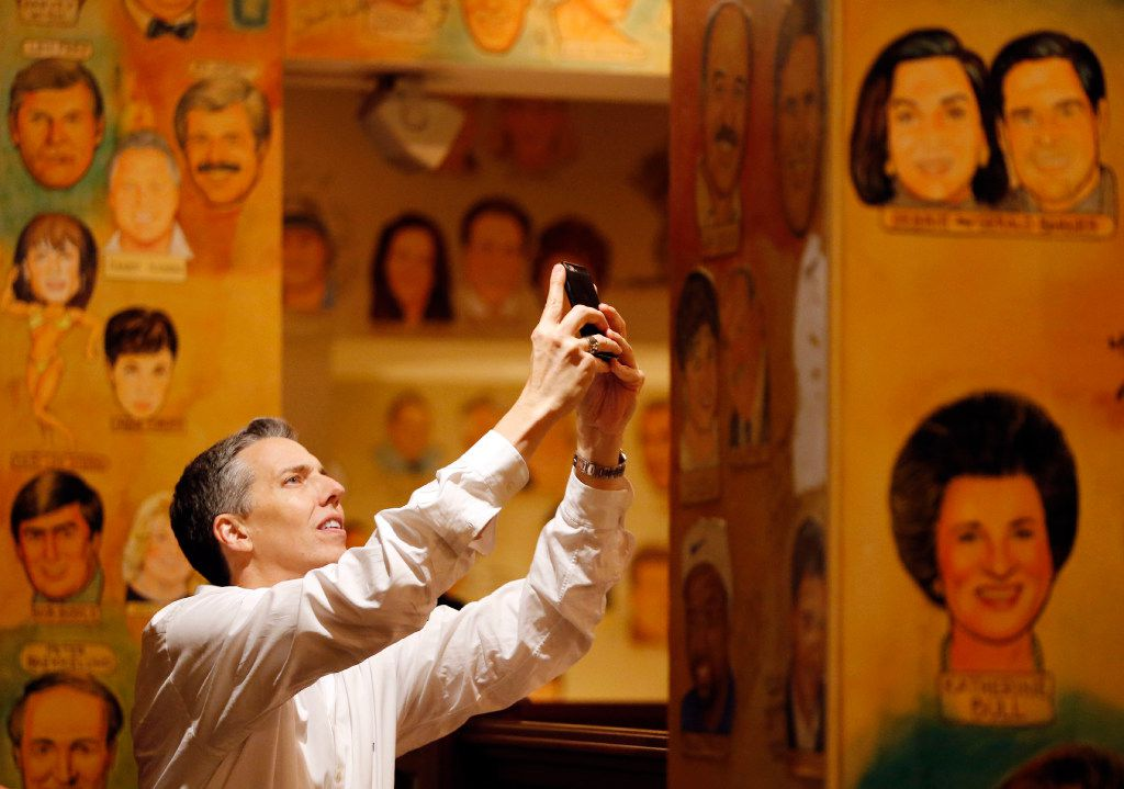 Gene Burkett takes photos of some of the artwork on the last day of business at the Palm Restaurant in Dallas on Friday. The Palm closed after 33 years in business.