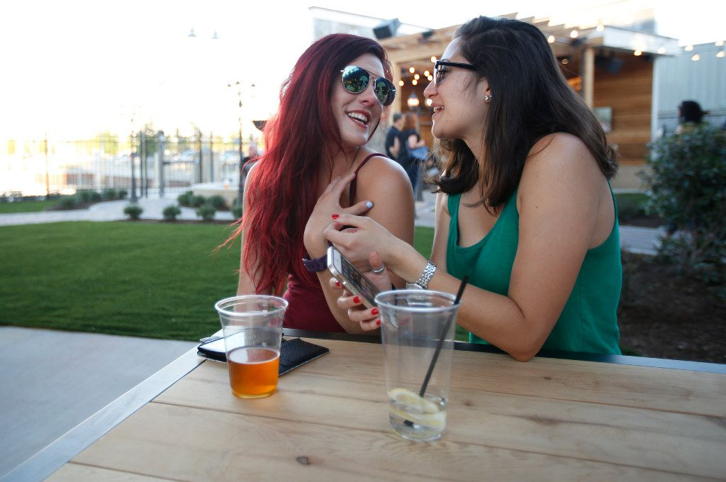 Ashley Cullinan (left) and Pilar Restrepo share a laugh as they watch Vandoliers perform at Lava Cantina in The Colony, Texas, Thursday, May 11, 2017.