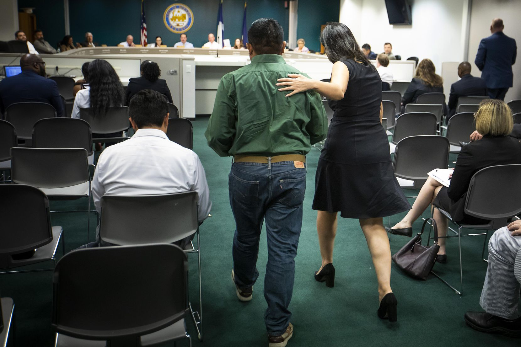 Ana Gonzalez, a policy advocate for Workers Defense Project, put her hand on Agustin Villanueva's shoulder as he prepared to testify to state lawmakers about wage theft during a hearing in Houston on July 24, 2018. Villanueva said he was not paid for repairing houses after Hurricane Harvey.
