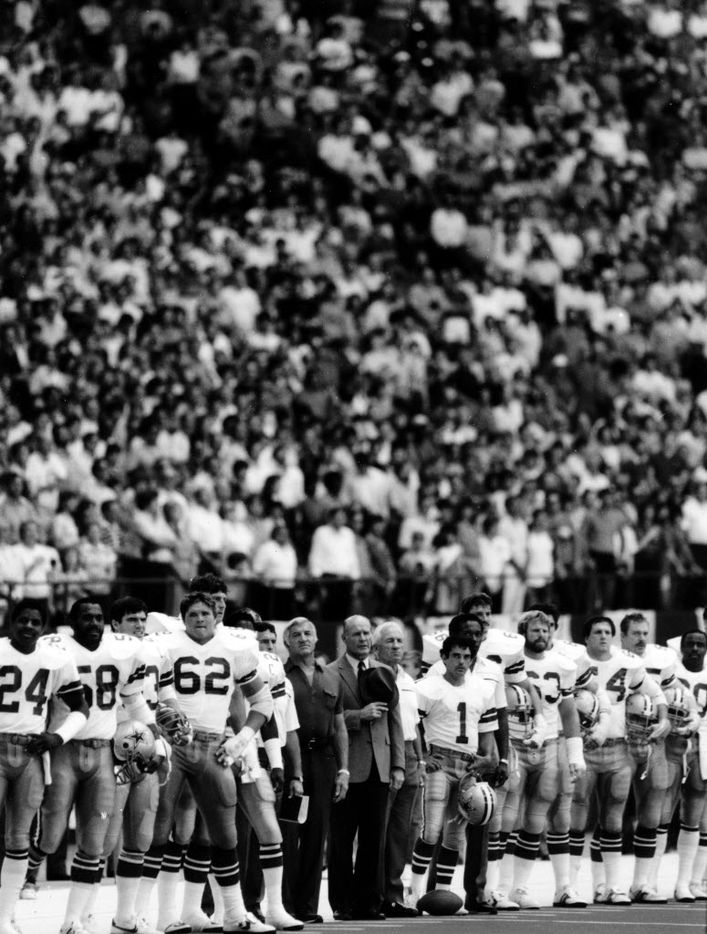 The Cowboys stand for the national anthem in 1983.