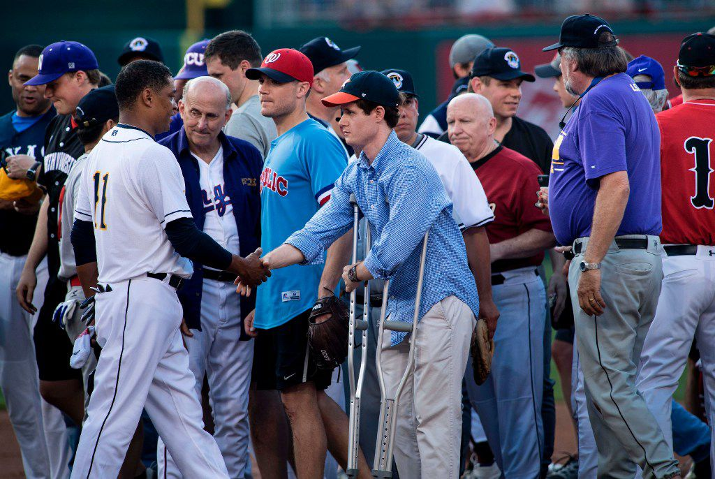Congressional staff member Zack Barth (C), who was wounded in yesterday's shooting, is greeted by the Democrat's pitcher Rep. Cedric Richmond (L), D-LA,  before the Congressional Baseball Game between Democrats and Republicans at Nationals Stadium June 15, 2017 in Washington, DC. This year's congressional charity baseball game is proceeding after a rifle-wielding critic of President Donald Trump opened fire June 14, 2017 on US lawmakers practicing for the charity event, seriously wounding a top Republican congressman and three others before he was killed by police. / AFP PHOTO / Brendan SmialowskiBRENDAN SMIALOWSKI/AFP/Getty Images