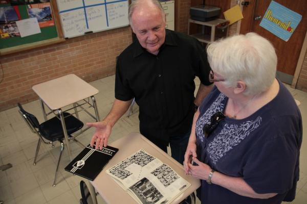 Bishop Lynch alumni John Ganter (left) and Joan Ellinger Bertucci share memories from Bishop Lynch yearbooks. President John F. Kennedy's assassination impacted both Ganter's and Bertucci's lives.